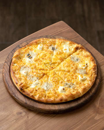 Whole Cheese Pizza with melted parmesan and mozzarella on wooden cutting board. Vegan or vegetarian meal. Italian food. Vertical format. Copy space on top of image. Reklamní fotografie