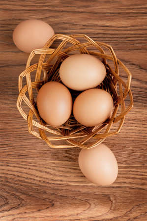wooden table top view: Eggs in a basket on wooden table. Top view