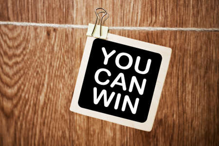success concept: You Can Win. Written Motivation Concept on Board Stock Photo