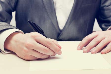 Close-up Van Zakenman Hand schrijven op een papier op zijn werkplek