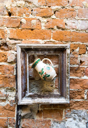Jug in old picture frame hangs on old brick wall