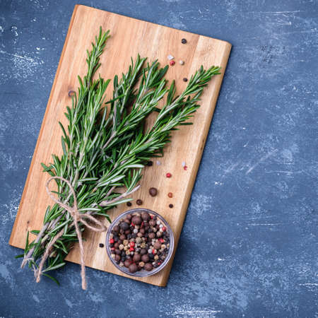 Rosemary branches tied with string on concrete dark blue table background. With pepper blend on wooden cooking board. Top view, flatlay. Square image. Cooking concept. Stock Photo