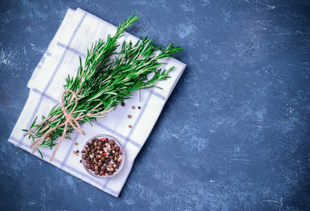 Rosemary branches tied with string on concrete dark blue table background. With pepper blend on white cloth napkin. Top view wtih copyspace. Cooking concept. Stock Photo