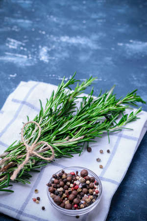 Rosemary branches tied with string on concrete dark blue table background. With pepper blend on white cloth napkin. Cooking concept.