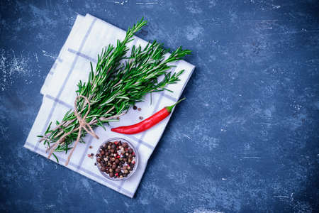 Rosemary branches tied with string on concrete dark blue table background. With pepper blend and chili pepper on white cloth napkin. Top view, flatlay. Cooking concept.