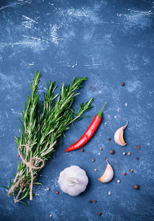 Rosemary branches tied with string on concrete dark blue table background. With pepper blend, chili pepper and garlic. Top view, flatlay. Cooking concept. Stock Photo