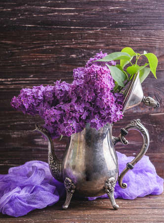 Bouquet of purple lilac flowers in vintage decorative teapot with purple dyed gauze fabric. Dark brown wooden background. Spring romantic flowers decoration. Vintage style.