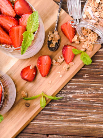 Yogurt parfait in glasses with granola, strawberries and mint leaves. On wooden board. Healthy breakfast concept. Rustic wooden table background. Stock Photo