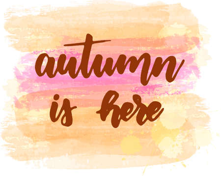 Autumn is here - handwritten modern calligraphy lettering on abstract brushed watercolor background. Season illustration. Orange and pink colored.
