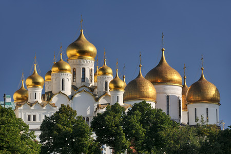 cupolas: The view of magnificent bulbous (onion-shaped) domes covered golden leaf of ancient cathedrals in Moscow Kremlin from Sofiyskaya Embankment across Moskva River.  At the left %u2013 domes of Blagoveschensky Sobor (Cathedral of Annunciation) constructed in  Stock Photo