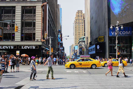People are walking in Manhattan with yellow cab on sunday morning