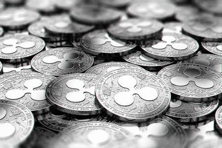 Stack of silver Ripple XRP coins in blurry closeup with copy space above in blurred area. 3D rendering Archivio Fotografico