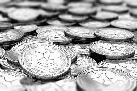 Stack of silver LISK coins in blurry closeup with copy space above in blurred area. 3D rendering