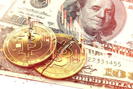 Two broken Bitcoin coins laying on dollar bills. Red candles of stock exchange diagram as a symbol of crash. 3D rendering Stock Photo
