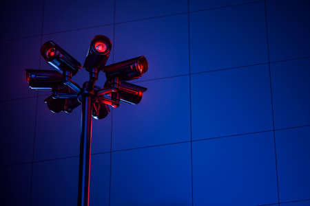 Cctv pylon with several cameras on a blue wall during night. Copy space included. Safety and monitoring concept. 3D rendering Zdjęcie Seryjne