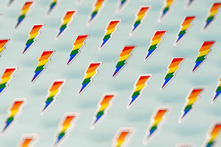 Blurry closeup shot on LGBT lightning bolt rainbow pride symbol isolated on green background. Gay, Lesbian and sexual minority fight for their rights symbol concept. 3D rendering Imagens