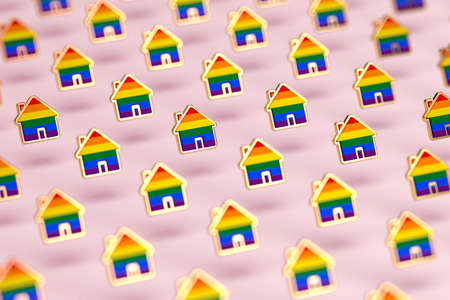 Blurry closeup shot on group of gay pride rainbow in a home shape isolated on pastel pink background. LGBTQ people rights to live together concept. 3D rendering