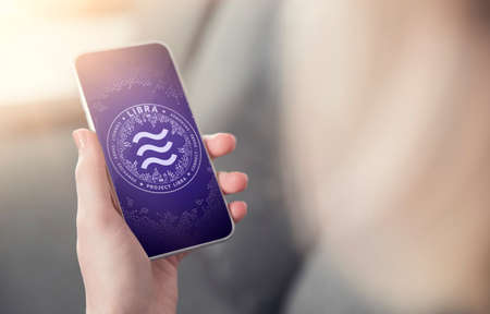 Hand holding smartphone with Libra symbol on screen. New era in e-commerce, on-line payments and e-business concept. New virtual money - 3D rendering