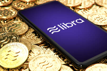 Smartphone with Libra logo on the screen is laying down on Libra concept coins - Image