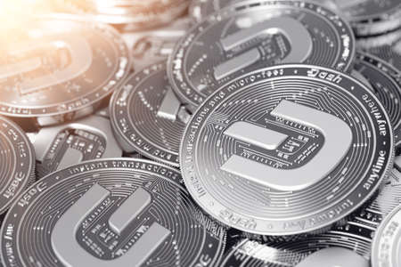 Stack of silver Dash coins (with 2019 updated logo) in blurry closeup. 3D rendering