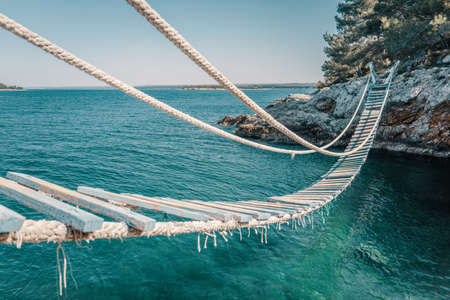 Rope bridge over a cliff in Punta Christo, Pula, Croatia - Europe. Travel photography, perfect for magazines and travel destination articles. Imagens