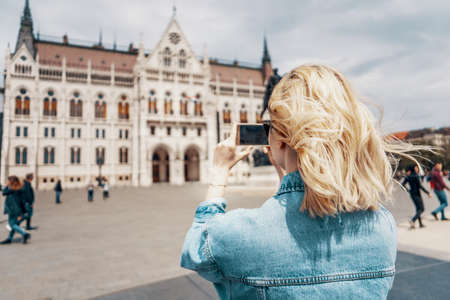 Young female tourist takes pictures of Hungarian Parliament with her smartphone on beautiful sunny day. Shot from behind. European travel destinations concept