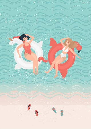 Two girlfriends in bathing suits swim on swimming circles of a unicorn and a flamingo in the sea near the beach