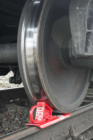 inhibit: Rusty and polished freight train wheel on railroad track. Train shoe propped wheel train.