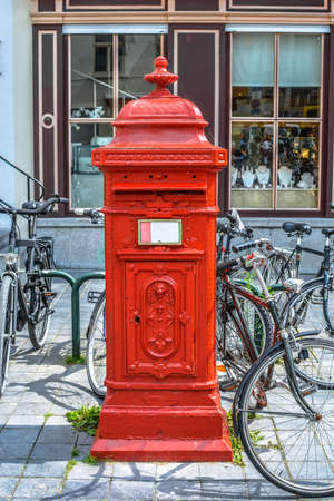 posting: young woman posting letters in red mailbox outdor