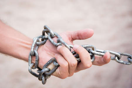 Hand with CHAIN metal and sand desert