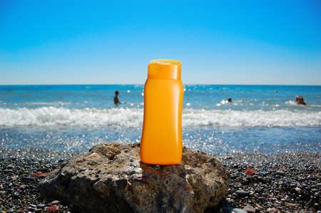 Tube with sun protection on beach of ocean   Stock Photo