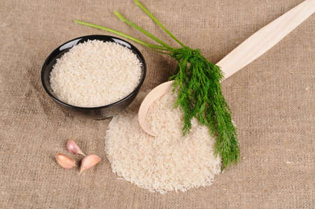 Rice with dill and spoon on the canvas photo