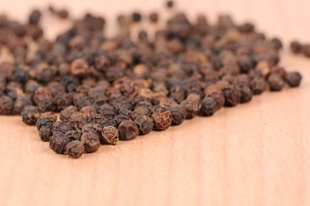 Black pepper on the wooden cutting board photo