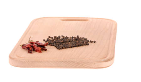 black and red pepper on the wooden cutting board photo