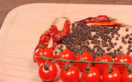 Black pepper red pepper and tomato  on the wooden cutting board photo