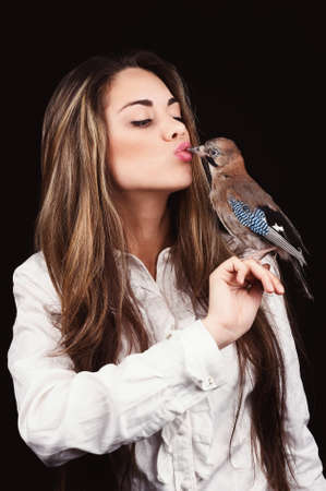 Portrait of beautiful girl in fashion style with bird on the hand photo