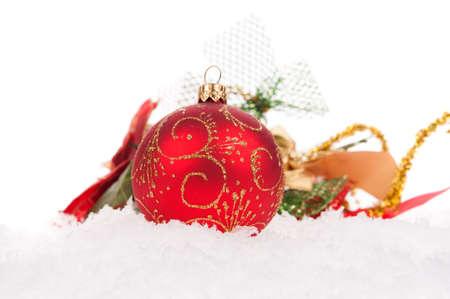 Esfera vermelha do Natal com neve no fundo branco