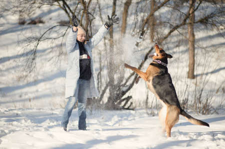 romp: Girl playing with dog on the snow