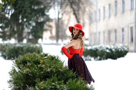 attractive girl in red hat outdoor on the snow
