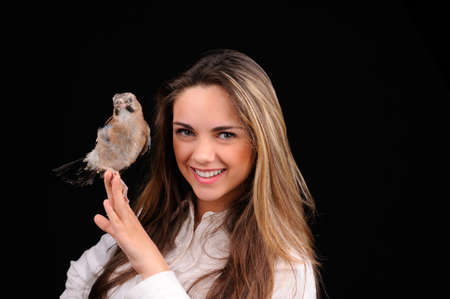 animal skin: Portrait of smiling girl with bird on the hand