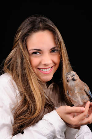 Portrait of smiling girl with bird on the hand photo