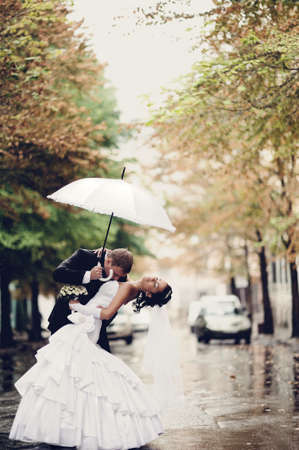 Bride and groom kissing under white umbrella photo