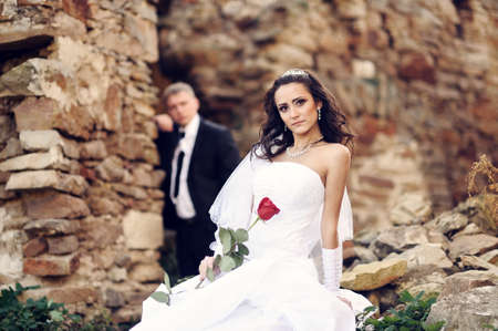 Bride and groom near ancient castle photo