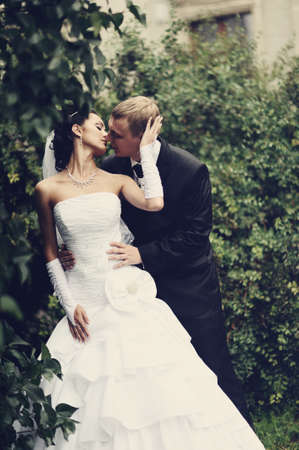 Bride and groom kissing outdoor photo