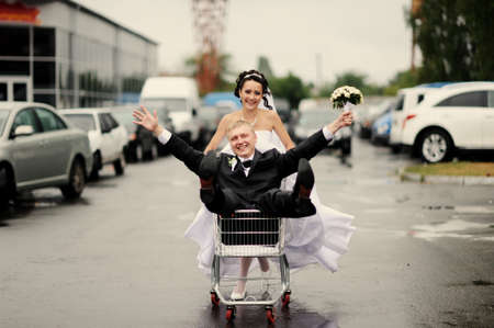 happy bride pulling a fiance in the pushcart photo