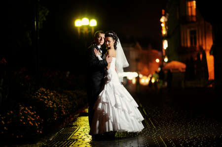 Bride and groom together at night walk photo