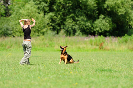 Girl playing with dog on green grass photo