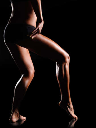 Beautiful female body of athlete on a dark background  photo