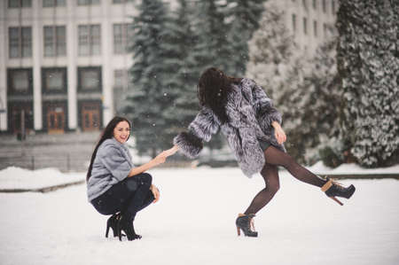 frozen winter: funny girls enjoying winter weather  - with film effect with small grain