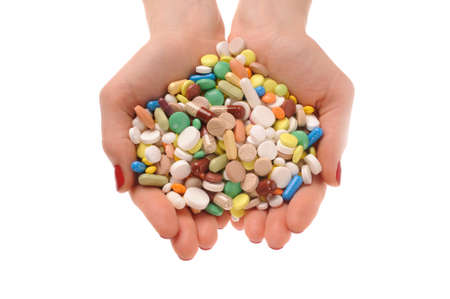 Stack of different pills in the hands over white background